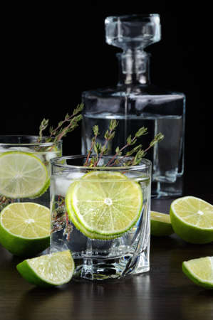 Cocktail with white rum and tonic, a slice of lime and thyme