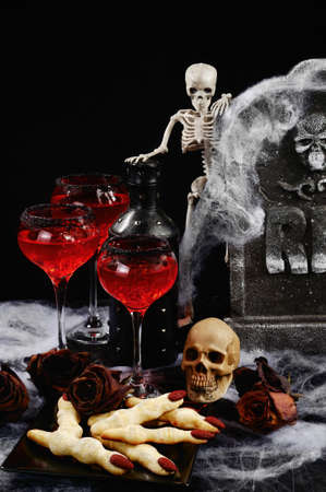 Bloody cocktail with ice on the table with a snack of cookies witch fingers in honor of Halloween.  Idea  Drinks Party Stock Photo