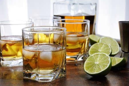 Alkoholcocktail mit Brandy, Whisky oder Rum mit Ginger Ale, Limette und Eis in Gläsern
