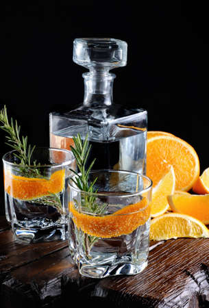 Cocktail classic Dry Gin with tonic and orange zest with a sprig of rosemary on a wooden board with  slices   juicy orange