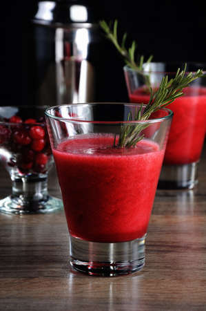Freshly made cranberry smoothie with a sprig of rosemary