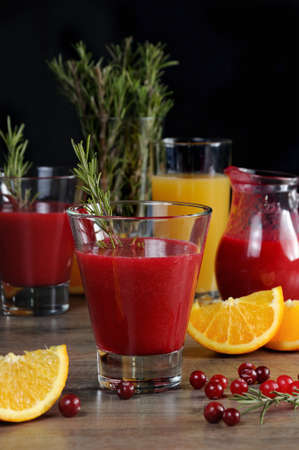 Freshly prepared cranberry fruit-drink with orange juice and a sprig of rosemary