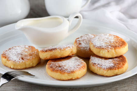 Breakfast. Cheese pancakes with sour cream sprinkled with powdered sugar on a white plate.