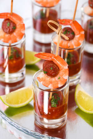 Appetizer of shish kebab with shrimps and chorizo sausages with barbecue sauce in a glass Stock Photo
