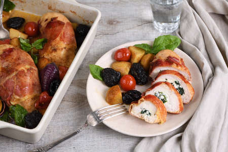 Sliced chicken stuffed with goat cheese with spinach, wrapped in prosciutto, with a side dish of baked potatoes, tomato and dried prunes