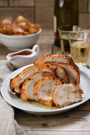 Sliced into slices baked turkey at the dinner table