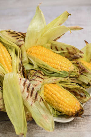 Delicate, juicy corn on the cob in husk cooked grilled