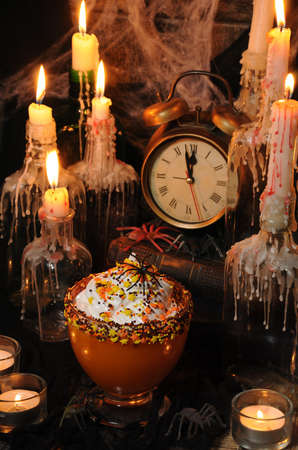 Bowl with pumpkin dessert with whipped cream on the table among the scenery for Halloween