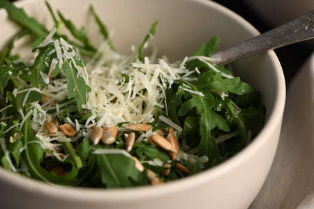 Arugula salad with sunflower kernels and sprinkled with grated parmesan