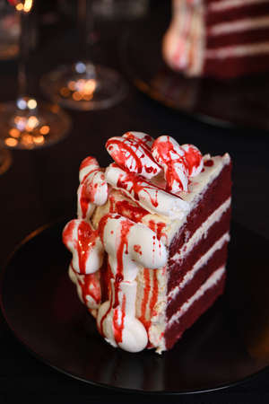 A piece of creepy cake (red velvet), decorated with meringue bones and drenched in blood. Great idea than treating guests. Close-up.