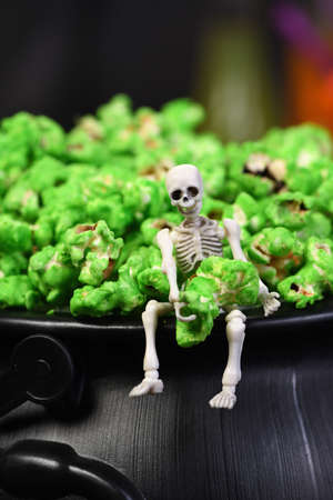 A skeleton sits on the edge of a cauldron and holds in its hands a green sweet popcorn. Close-up. Halloween treats. Foto de archivo