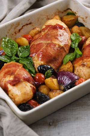 Chicken breast stuffed with goat cheese with spinach, wrapped in prosciutto, with slices of baked potatoes, tomatoes, and dried prunes.