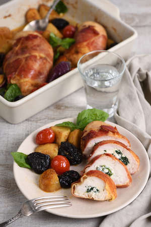 Sliced chicken breast stuffed with goat cheese with spinach, wrapped in prosciutto, with a side dish of baked potatoes, tomato and dried prunes Reklamní fotografie