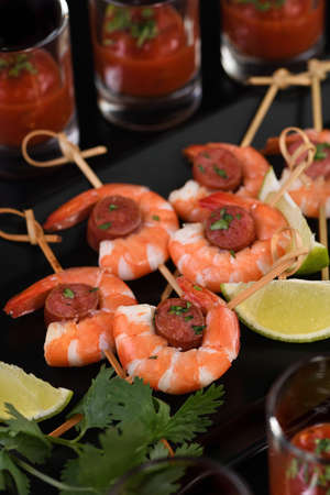 Appetizer of shish kebab with shrimps and chorizo sausages with barbecue sauce in a glass