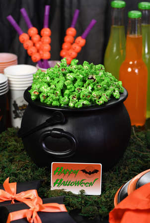 Cauldron green sweet popcorn for ghouls and zombies. Halloween treat Foto de archivo