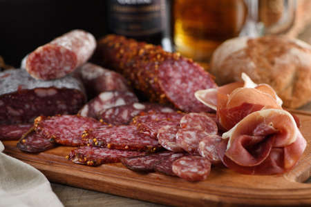 Antipasti dish with bacon, jerky, salami, crispy grissini with cheese. A meat appetizer is a great idea for a beer.