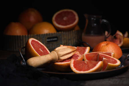 Slices of fresh grapefruit prepared for making fresh squeezed juice on a platter, dark background