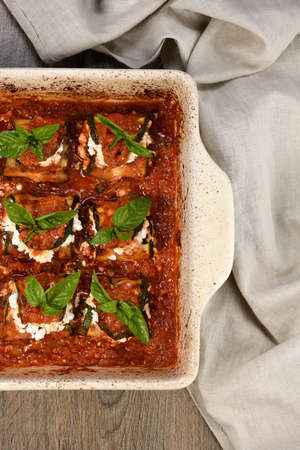 Baked zucchini rolls stuffed with ricotta and basil under tomato-onion-carrot gravy in a pan
