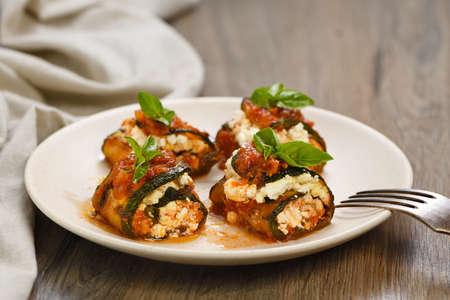 Baked zucchini rolls stuffed with ricotta and basil under tomato-onion-carrot gravy