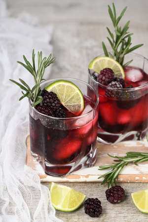 Two glasses of delicious refreshing lemonade with blackberry, ice and lime, decorated of rosemary. Cocktail on light table
