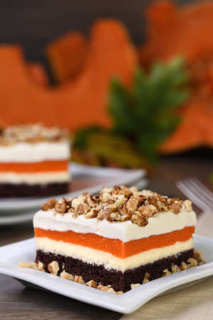 Pumpkin pie - light, creamy dessert with cheese cream and pumpkin layers topped with chopped nuts