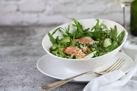 Vegetable salad from arugula, avocado and cucumber pieces with the addition of tender salted salmon, seasoned sesame seeds