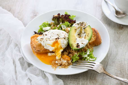 A healthy and balanced breakfast plate. Benedict's egg spreads on a toasted toast with half an avocado, quinoa and lettuce, seasoned spices and yogurt dressing. Enjoy the most important meal of the day