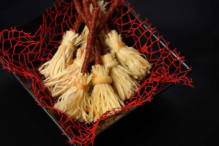 Witches Broom of smoked cheese suluguni and salami. Original idea Halloween snack.