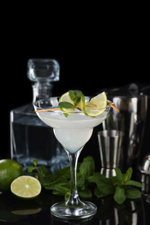 Tequila, Citrus liquor, lime juice - this is a Margarita cocktail. A of lime with a sprig of mint decorates a glass. Dark moody food