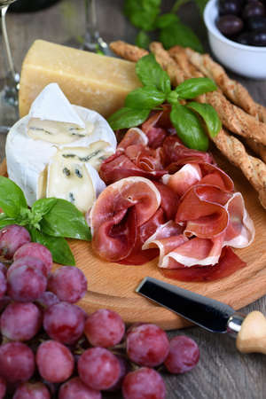 Antipasto. Wine set snacks of dried ham, brie cheese with mold, parmesan with grissini, olives and pink grapes.
