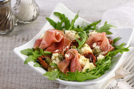 Arugula salad, prosciutto with sun-dried tomatoes, slices of mozzarella, capers, seasoned with olive butter and parmesan. A dish for those who monitor their health Reklamní fotografie