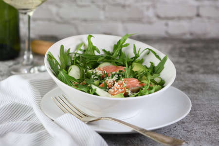 Vegetable salad from arugula, avocado and cucumber pieces with the addition of tender salted salmon, seasoned sesame seeds Reklamní fotografie