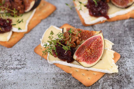 Cracker with a slice of camembert, jam, figs and nuts. A great snack idea for a holiday, picnic or party. Reklamní fotografie