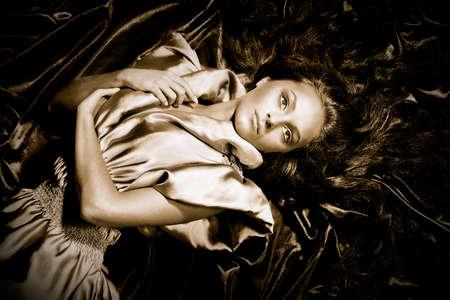 긴 검은 머리카락을 가진 어린 소녀 포즈 무지개 빛깔의 직물