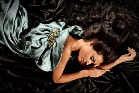 Young girl with long black hair lying poses no iridescent fabric Stock Photo