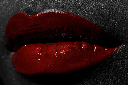 The lips of a young girl covered with red paint