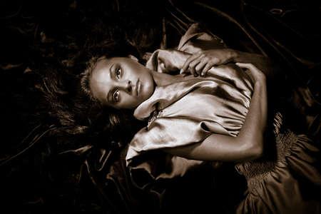 Jong meisje met lange zwarte haren liggen vormt geen iriserende weefsel  Stockfoto