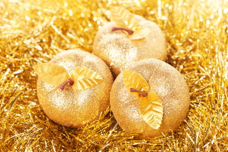 Golden apples lying on the golden background photo