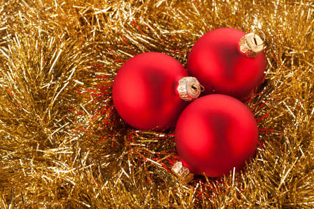 Red Christmas balls lying on a golden background photo