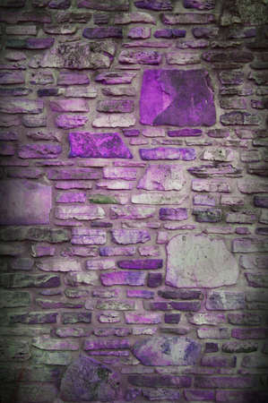on gray: old stone background, fun colorful design with gray blocks and black vignette border, and purple rocks, background has abstract random pattern of stones in rock wall