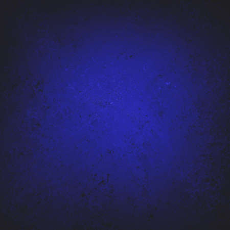 textured dark blue paper background design, spotlight center and black vignette frame, blue painted wall surface photo