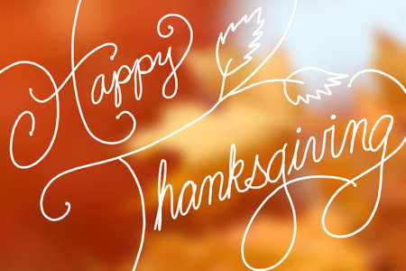 Happy Thanksgiving text design on blurred orange maple leaves Stockfoto