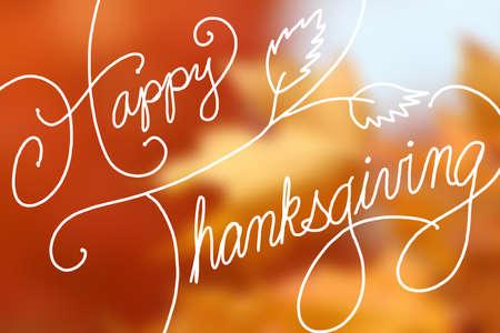 Happy Thanksgiving text design on blurred orange maple leaves Standard-Bild