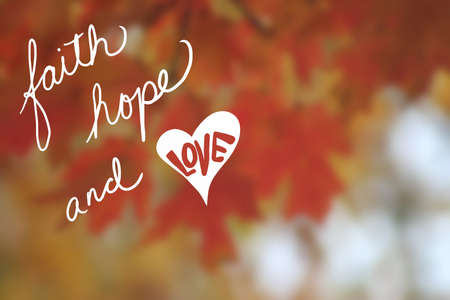 faith hope and love quote in white typography letters with cute heart on warm orange and gold color leaves and blurred bokeh background, inspirational statement saying