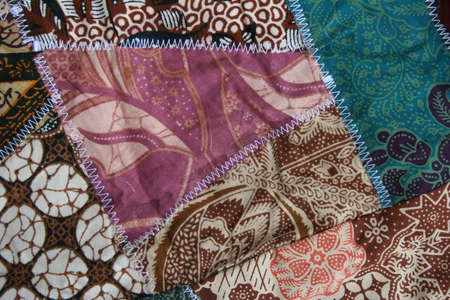 Batik material background, Indonesian material pieced together with white zigzag stiches in crazy quilt design in colorful blue green pink and brown colors