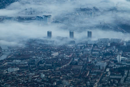 The three buildings of Grenoble in the morning fog.