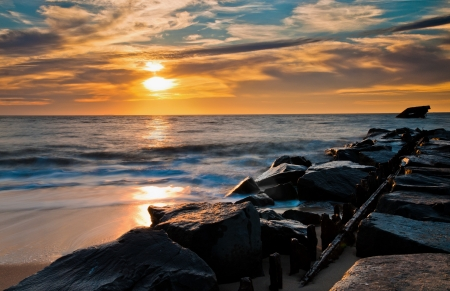 shore: Sunset over a jetty and the USS Atlantus Shipwreck at Sunset Beach, Cape May, New Jersey   Stock Photo