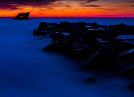 Seen here is the the U S S  Atlantus shipwreck and a jetty at sunset, seen from Sunset Beach, Cape May, New Jersey   photo