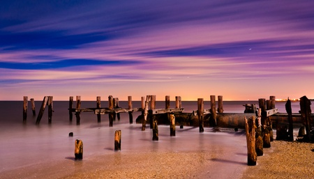 Clouds move through the sky behind pier pilings on a moonlit night at Sunset Beach, Cape May, New Jersey    photo
