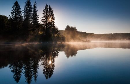 west virginia trees: The sun rising behind pine trees and illuminating morning fog on Spruce Knob Lake, in Monongahela National Forest, West Virginia